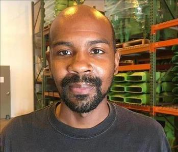 Bald man with facial hair wearing a black shirt and smiling