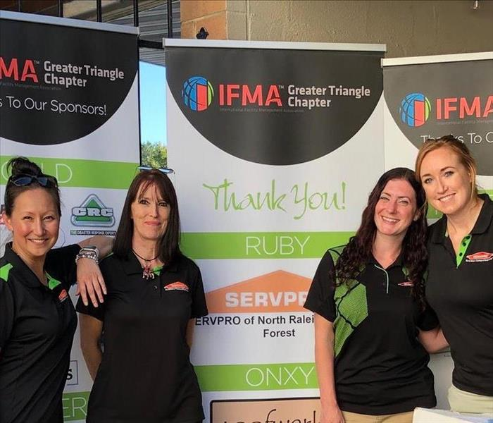 Four SERVPRO employees standing in front of a IFMA posters.