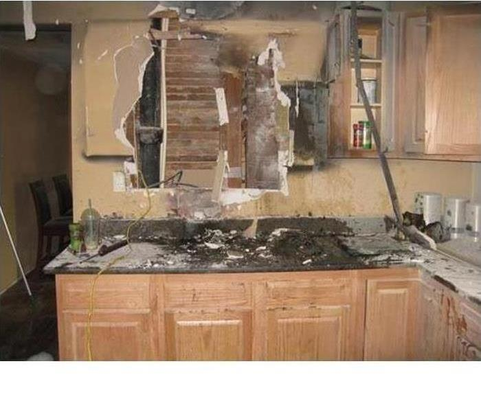 A kitchen under full demolition after a fire